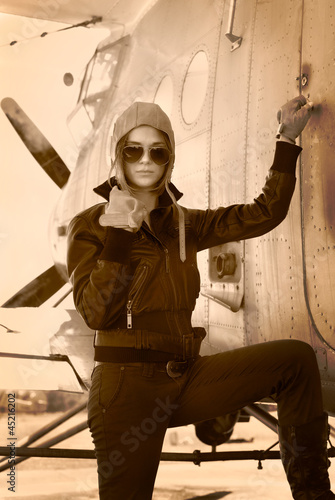 Beautiful girl in jacket standing next to war aircraft.