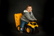 Young boy playing on toy dump truck