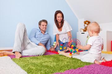 Familie spielt mit baby im kinderzimmer