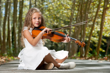 Young girl playing violin in the woods.