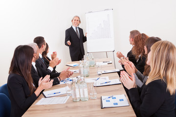 Business Team Sitting At Table And Applauding