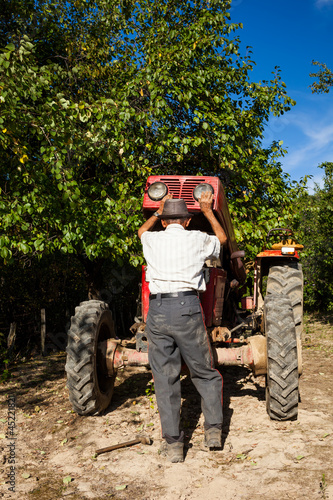 Senior farmer repairing his tractor