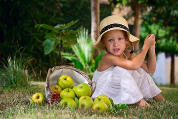 Девочка сидит на траве с корзиной яблой