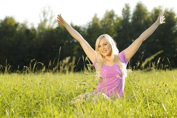 Blonde hübsche Frau in lila Shirt streckt sich in grüner Wiese
