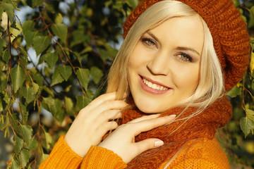 Hübsche blonde Frau mit Mütze und Schal im Herbst