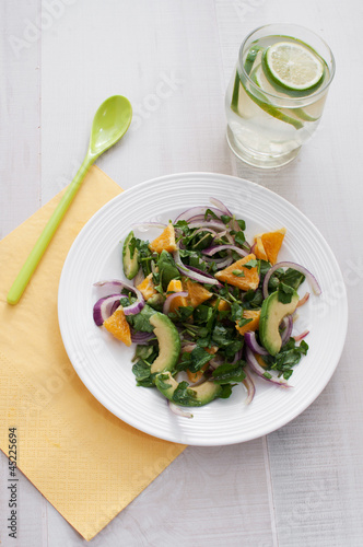 Salad with onion, watercress, avocado and oranges top view