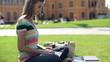 Happy female student working on laptop on campus
