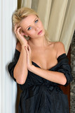 Beautiful woman in black silk robe with naked shoulders.