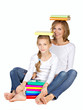 mother and daughter sitting on the floor with many books