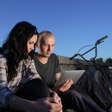 beauty girl and boy with laptop pc outdoors