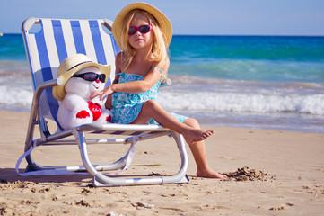 девочка сидит на шезлонге на берегу моря