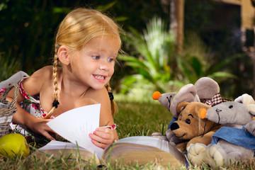 девочка читает книгу с игрушками на природе