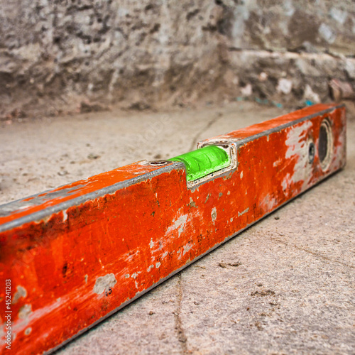 Dirty spirit level on a concrete surface