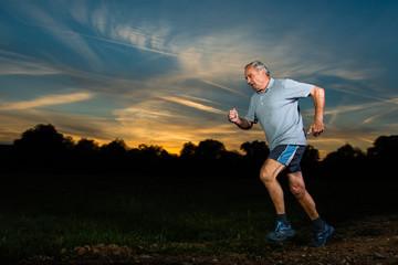 Senior joggt vor sonnenuntergang