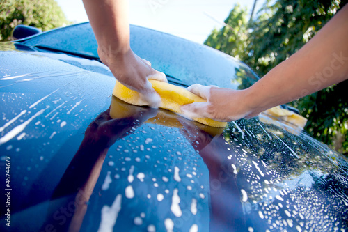 2 hands hold sponge over the car for washing