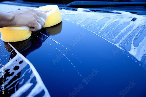 hand hold sponge over the car for washing
