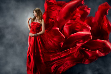 Beautiful woman in red waving flame silk dress