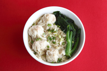 a bowl of noodle and dumpling soup