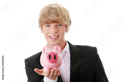 Young businessman holding piggy bank