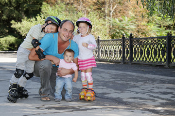 happy family - father and three children - on roller skates outd