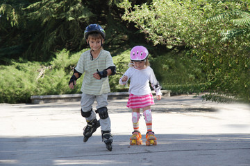 two happy children on roller blades outdoors