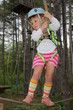 young girl in adventure park wearing mountain helmet and safety