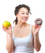 Diet. Beautiful Young Woman choosing between Fruit and Donut
