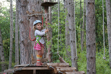young child girl in adventure park wearing mountain helmet and s