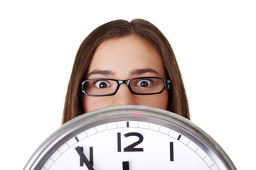Young woman holding office clock