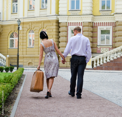 Couple walking with woman carrying luggage