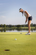 Girl golfer putting ball on green.