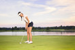 Girl golfer putting.