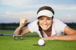 Joyous girl golfer looking at ball dropping into cup.