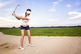 Woman golf player in sand trap preparing to hit the ball.