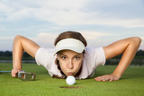 Girl golf player blowing ball into cup.