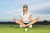 Girl golfer sitting in yoga posture on golf course.