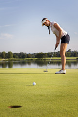 Girl golfer putting ball on green.