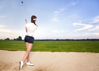 Girl golf player in bunker chipping ball.
