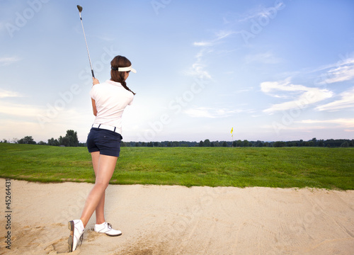 Girl golf player in bunker chipping ball.