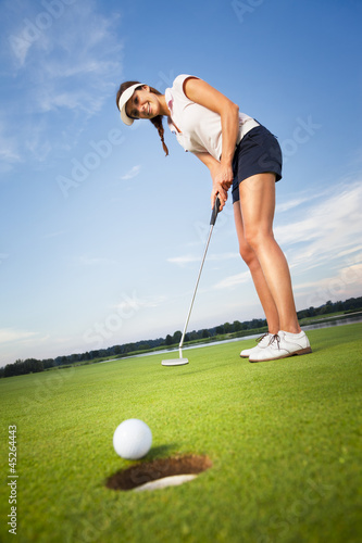 Happy girl golfer putting ball into hole.