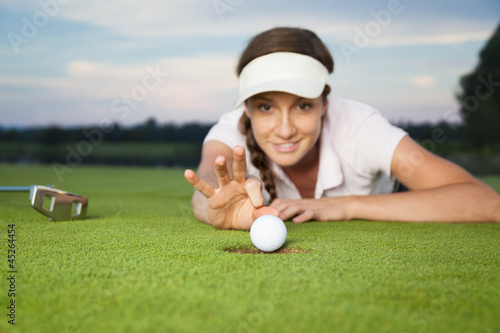 Girl golfer making a trick on green.