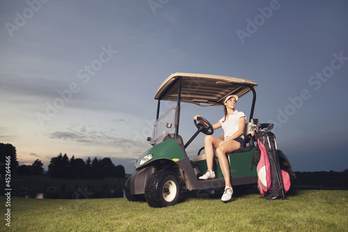 Golfer sitting in golf cart at twilight.