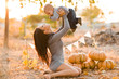 Happy mother and son with pumpkin on autumn leaves