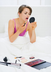 Young woman sitting in bed and applying makeup