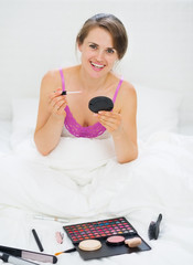 Happy young woman sitting in bed and applying makeup