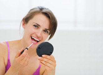 Portrait of happy young woman applying makeup