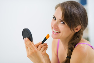 Smiling young woman applying makeup