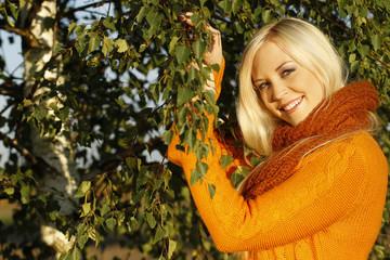 Hübsche blonde Frauin der Natur  lächelt in die Kamera