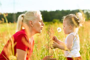 Mutter mit Tochter in der Wiese und pustet Löwenzahn
