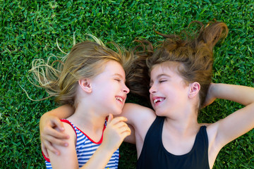 sisters kid girls smiling lying on garden grass